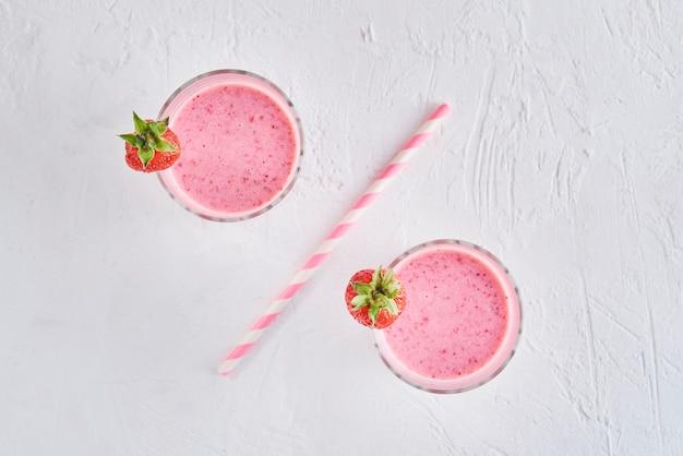Due bicchieri con frullato di fragole separati da cannuccia come segno di percentuale. concetto di cibo sano
