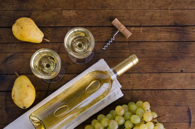 Due bicchieri di vino, una bottiglia di vino e pere mature su un tavolo di legno con spazio per copiare il testo. vista dall'alto. disposizione piatta.