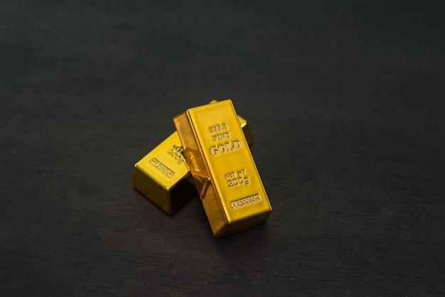 Due lingotti d'oro su un tavolo di legno nero.