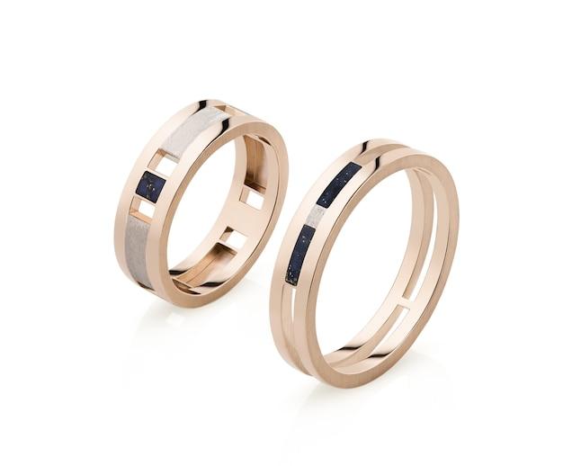 Due anelli d'oro su sfondo bianco isolati, in posizione verticale