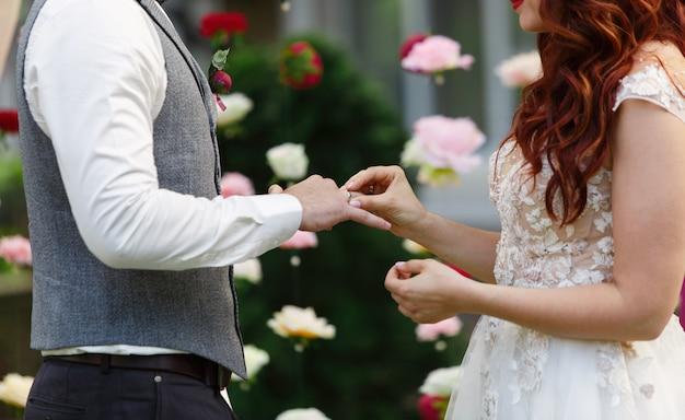 Due anelli di nozze d'oro. la sposa indossa l'anello nuziale dello sposo. sposi con anelli sulle dita cerimonia di matrimonio all'aperto.
