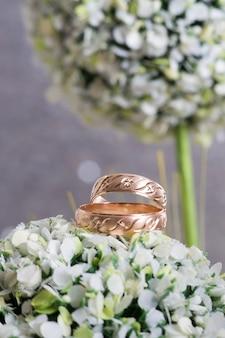 Due anelli di nozze d'oro su fiori verdi