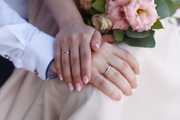 Due anelli di nozze d'oro sulle mani da vicino. gli sposi con fedi nuziali sulle dita da vicino.