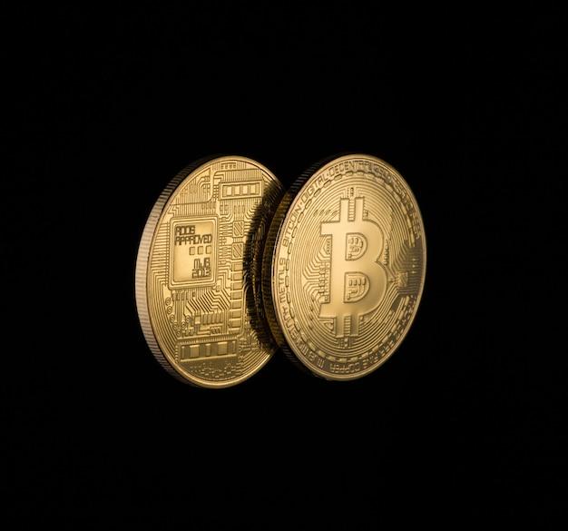 Due bitcoin dorati su sfondo nero con spazio di copia. denaro elettronico isolato