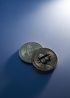 Due bitcoin dorati isolati su sfondo blu ravvicinato con spazio di copia, concetto di crescita e caduta di criptovaluta