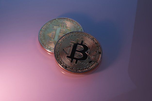Due bitcoin dorati isolati sul primo piano porpora rosa del fondo con lo spazio della copia