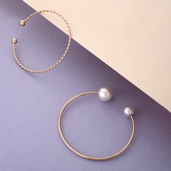 Due braccialetti d'oro con perle su sfondo beige e viola con spazio per le copie