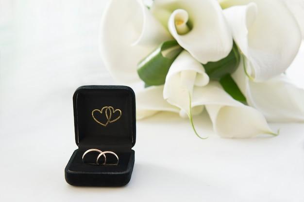 Due anelli di nozze d'oro su sfondo bianco. bouquet di calle sullo sfondo