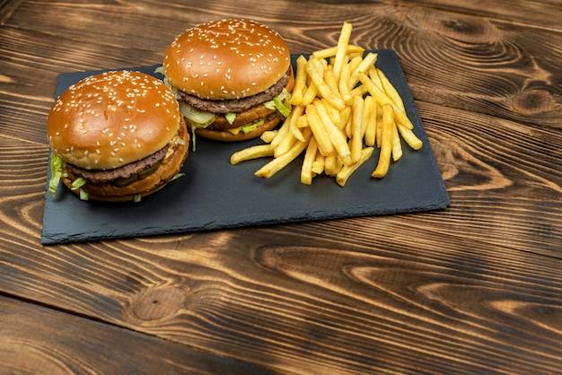 Due deliziosi hamburger gourmet con fette di patatine fritte su un bordo nero su un tavolo di legno. fast food