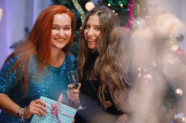 Due donne graziose si rallegrano con una confezione regalo vicino a un albero di natale. le donne ridono, sorridono, posano. filtro antirumore e grana speciale vintage, luci sfocate.