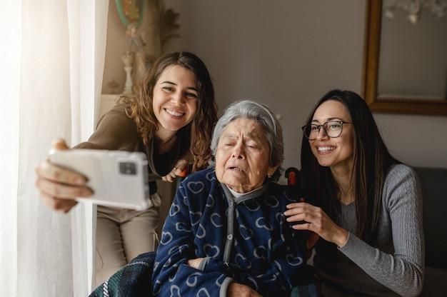 Due nipoti con la vecchia nonna in sedia a rotelle che scattano una foto o hanno una videochiamata con volti sorridenti. nuovo normale, terza età, concetto di famiglia.