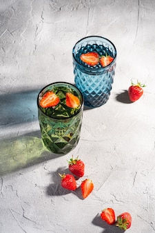 Due tazze di vetro geometriche verdi e blu con acqua fresca e frutti di fragola con raggi di luce ombra colorata su sfondo di cemento di pietra, vista angolare