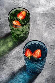 Due tazze di vetro geometriche verdi e blu con acqua fresca e frutta fragola