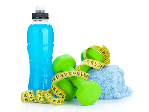 Due manubri verdi, metro a nastro e bottiglia per bevande. forma fisica e salute. isolato su sfondo bianco