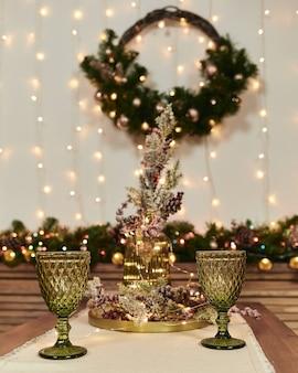 Due bicchieri verdi su un tavolo di legno. decorazioni natalizie