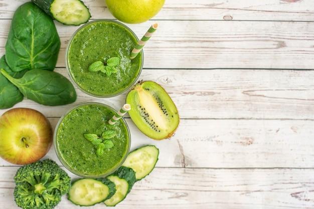 Due frullati verdi con ingredienti sul tavolo in legno chiaro. vista dall'alto. con copia spazio