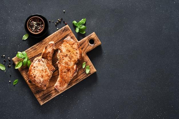 Due bistecche di maiale alla griglia con aglio e basilico su una tavola di legno su sfondo nero con spazio per il testo. vista dall'alto.