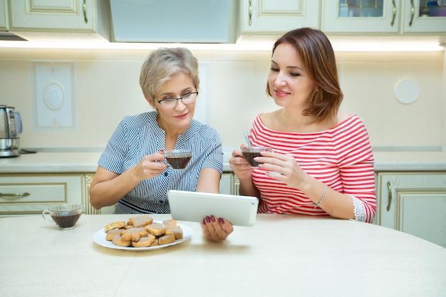Due donne adulte bevono caffè con biscotti in cucina e guardano il tablet