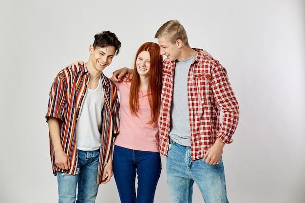 Due ragazzi e una ragazza in abiti colorati luminosi stanno sorridendo sullo sfondo bianco in studio