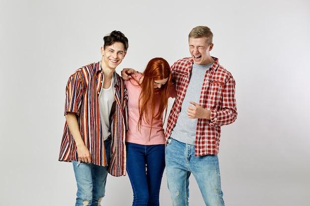 Due ragazzi e una ragazza in eleganti vestiti colorati luminosi stanno in piedi e sorridono sullo sfondo bianco white