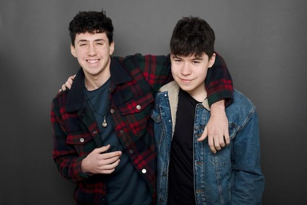 Due ragazzi che abbracciano come amici che guardano sulla fotocamera su uno sfondo grigio