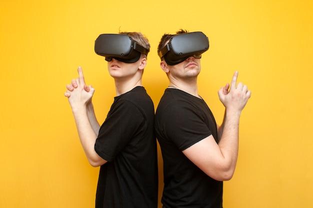 Due ragazzi con gli occhiali vr su uno sfondo giallo, gli amici giocatori con gli occhiali per la realtà virtuale giocano uno sparatutto e tengono le armi