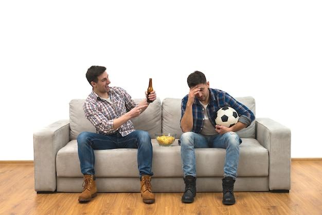 I due ragazzi con una birra e patatine guardano una partita di calcio sul divano