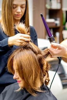 Due parrucchieri che usano il ferro arricciacapelli sui lunghi capelli castani dei clienti in un salone di bellezza.