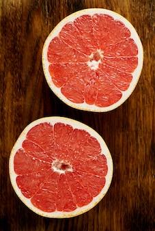 Due metà del pompelmo rosso, cerchi luminosi su un tavolo di legno scuro, agrumi
