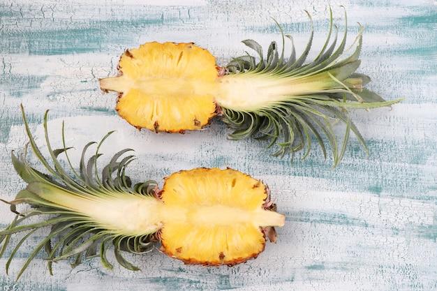 Due metà dell'ananas fresco sulla superficie azzurra. vista dall'alto.