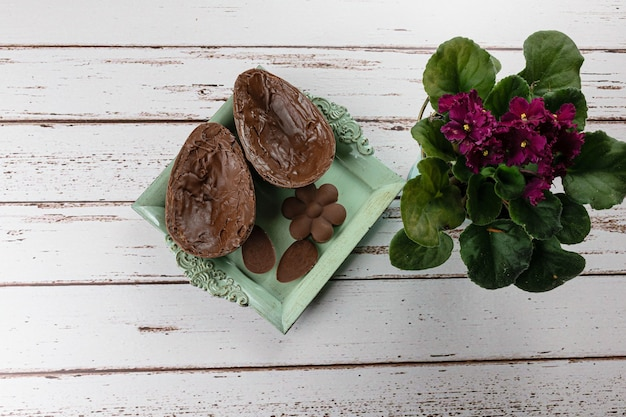 Due metà dell'uovo di pasqua del cioccolato, su un piccolo vecchio vassoio. accanto a mini cioccolatini e fiori.