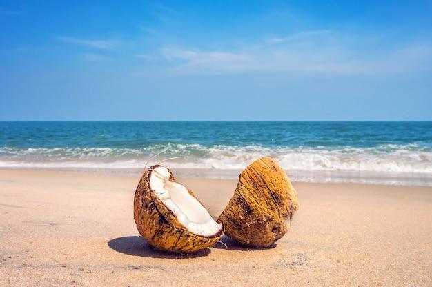 Due metà della noce di cocco marrone incrinata sulla spiaggia di sabbia bianca con il fondo del mare turchese