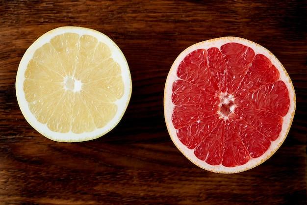 Due metà di pompelmo rosso e bianco, cerchi luminosi su un tavolo di legno scuro agrumi