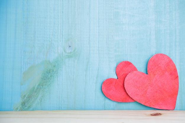 Due cuori fatti a mano contro fondo di legno rustico. concetto di amore.