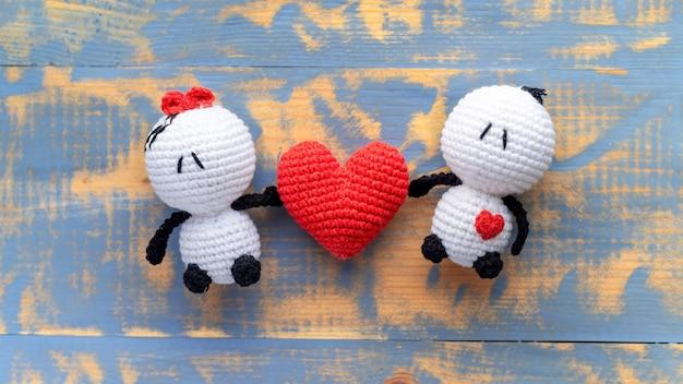 Due giocattoli lavorati a maglia fatti a mano e un cuore rosso. vista dall'alto