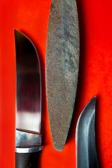 Due coltelli fatti a mano e una barra per l'affilatura su sfondo rosso