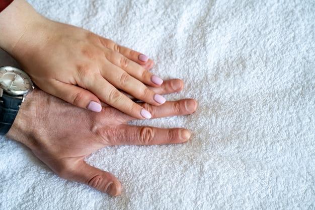 Due mani contro un lenzuolo bianco. uomo e donna. forza e amore della famiglia. cosmetici per prodotti per la cura della pelle. trattamento di eruzioni cutanee e prurito per le allergie.