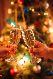 Due bicchieri tintinnio di mani con champagne, natale