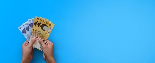 Due mani che tengono banconota vinta coreana su sfondo blu