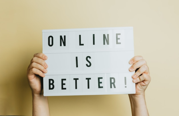 Due mani che tengono un cartello che dice che online è meglio su uno sfondo giallo pastello, concetto di stile e design, spazio copia, acquisto online ed e-commerce