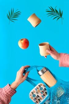 Due mani con tazza e foglia di palma, borsa a rete con scatola per il pranzo e pallone da tè volante. tè a perdere zero in fiasco di bambù isolato eco-compatibile. concetto zero rifiuti, levitazione surreale sulla parete blu