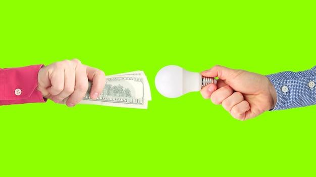 Due mani con banconote da un dollaro e una lampada a led su un verde brillante. pagamento per l'elettricità. acquista lampada a led. settore commerciale