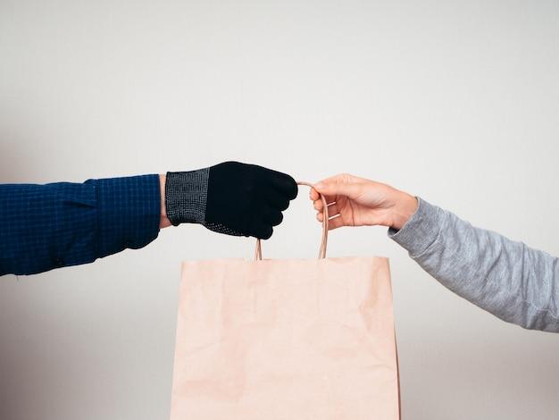 Due mani con un sacco di carta su uno sfondo bianco. concetto di consegna per la pandemia covid-19.