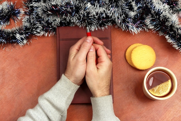 Le due mani con la penna rossa sdraiate su un taccuino sulla scrivania dell'ufficio con tè e biscotti