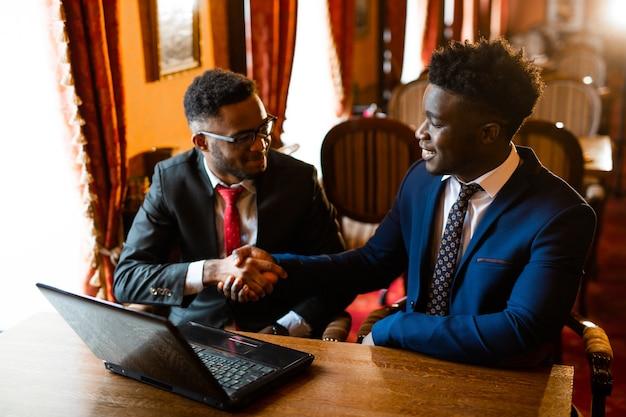Due bei uomini africani al chiuso con il portatile in stretta di mano