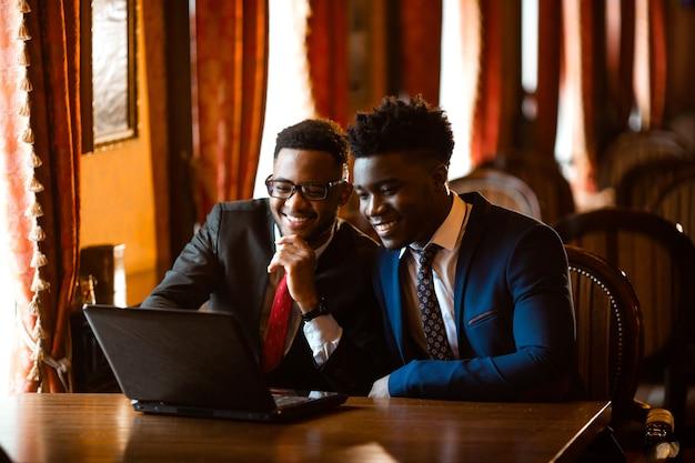 Due bei uomini africani al chiuso con il portatile