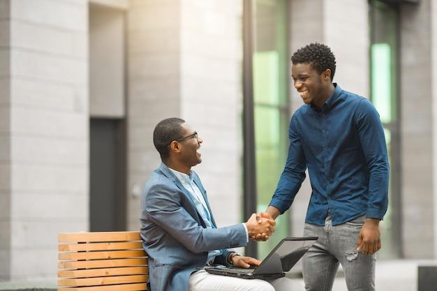 Due uomini africani belli vicino all'edificio