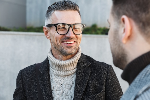 Due uomini belli che indossano cappotti trascorrono del tempo all'aperto, parlando