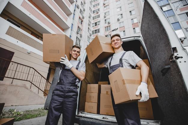 Due bei lavoratori in uniforme sono in piedi davanti al furgone pieno di scatole