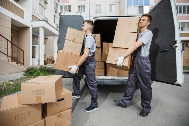 Due bei lavoratori in uniforme stanno scaricando il furgone pieno di scatoloni